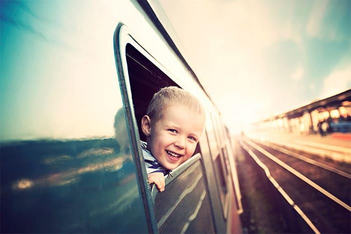 Kleiner Junge schaut aus einem Zugfenster hinaus.