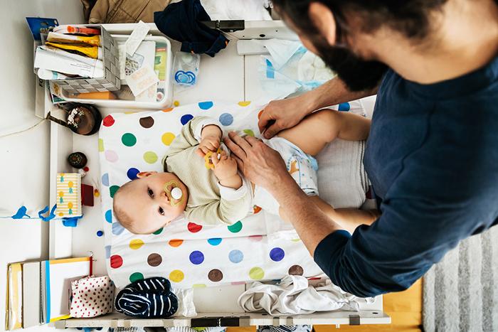 Kinder und Hämophilie A - Mann wickelt Baby